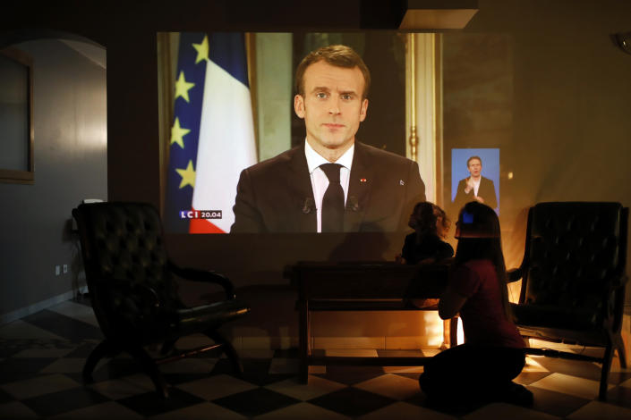 A woman and her daughter watch French President Emmanuel Macron during a televised address to the nation, in Lyon, central France, Monday, Dec. 10, 2018. Facing exceptional protests, French President Emmanuel Macron broke his silence Monday by promising broad tax relief for struggling workers and pensioners, and acknowledging his own responsibility for the nation's anger. (AP Photo/Laurent Cipriani)