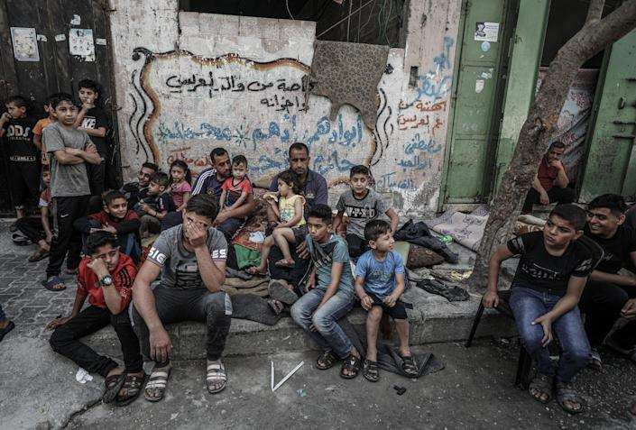 Palestinian Al Deyri family's children are seen at street after their home demolished by Israeli army's airstrikes in Gaza City, Gaza on May 17, 2021.