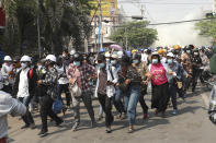 Protesters disperse as police fire tear gas during an anti-coup demonstration in Mandalay, Myanmar, Sunday, March 7, 2021. The escalation of violence in Myanmar as authorities crack down on protests against the Feb. 1 coup is raising pressure for more sanctions against the junta, even as countries struggle over how to best sway military leaders inured to global condemnation. (AP Photo)