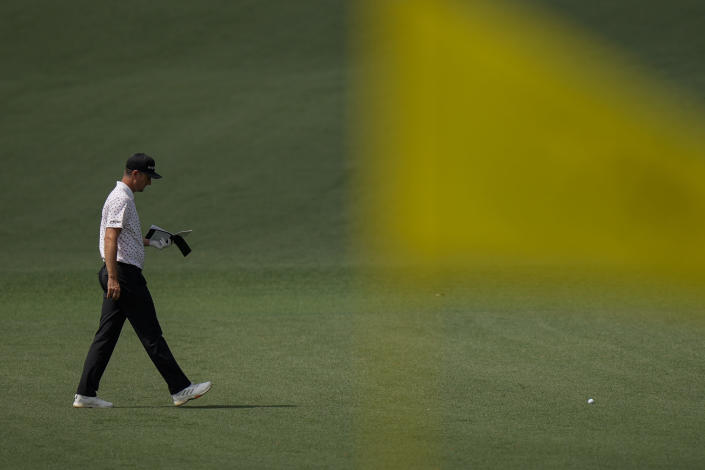 Justin Rose, of England, studies his course notes as walks to his ball on the second hole during the final round of the Masters golf tournament on Sunday, April 11, 2021, in Augusta, Ga. (AP Photo/Matt Slocum)