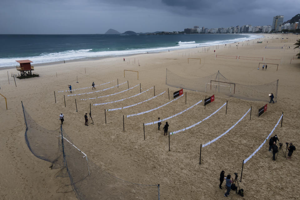 """Clotheslines holding white scarves on Copacabana beach represent those who have died of COVID-19 in Rio de Janeiro, Brazil, Friday, Oct. 08, 2021. The action was organized by the NGO """"Rio de Paz"""" to protest the government's handling of the pandemic as the country nears a total of 600,000 COVID-19 related deaths. (AP Photo/Lucas Dumphreys)"""