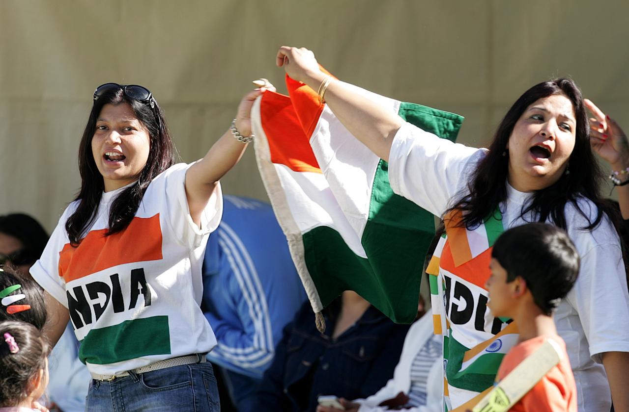 Supporters of the Indian cricket team wave their country's flag during the second one-day international ODI series between hosts Zimbabwe and India at Harare Sports Club on July 26, 2013. AFP PHOTO / Jekesai Njikizana.        (Photo credit should read JEKESAI NJIKIZANA/AFP/Getty Images)