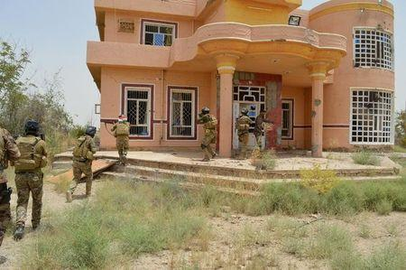 Iraqi security forces personnel walk with their weapons as they inspect a house south of Falluja, Iraq, June 6, 2016.  REUTERS/Stringer