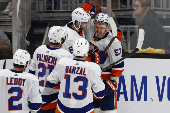 Teammates surround New York Islanders' Casey Cizikas after he scored the winning goal in overtime of Game 2 of an NHL hockey second-round playoff series against the Boston Bruins, Monday, May 31, 2021, in Boston. (AP Photo/Winslow Townson)