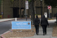 Pedestrian walk past a Campus Zone sign, which advises restricted access to approved students, faculty, staff, essential deliveries, testing and maintenance, on the Stanford University campus in Stanford, Calif., Wednesday, Sept. 2, 2020. With the coronavirus spreading through colleges at alarming rates, universities are scrambling to find quarantine locations in dormitory buildings and off-campus properties to isolate the thousands of students who have caught COVID-19 or been exposed to it. (AP Photo/Jeff Chiu)