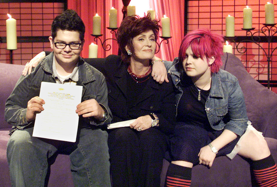 """Sharon Osbourne (C), wife of musician Ozzy Osbourne, poses for photographers with her son Jack and daughter Kelly in New York City, May 15, 2002. The Osbourne's announced that they are releasing a new album called """"The Osbourne Family Album"""" next month. The album features both old and new songs from all of the family members. REUTERS/Jeff Christensen JC/SV"""