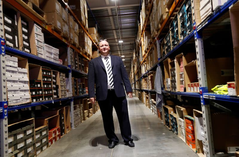 FILE PHOTO: Mike Ashley, founder and majority shareholder of sportwear retailer Sports Direct, stands between shelves of stock during a factory tour after the company's AGM, at the company's headquarters in Shirebrook