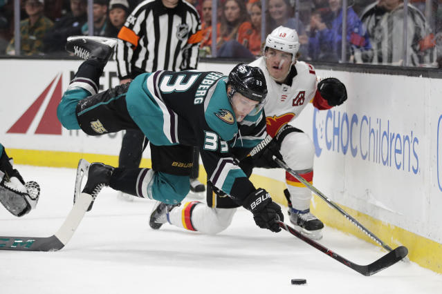 Anaheim Ducks' Jakob Silfverberg, left, of Sweden, loses his balance while moving the puck past Calgary Flames' Matthew Tkachuk during the first period of an NHL hockey game Wednesday, April 3, 2019, in Anaheim, Calif. (AP Photo/Jae C. Hong)