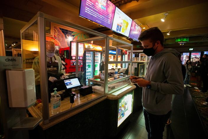 A moviegoer shops at concession stands retrofitted with plexiglass partitions before the movie