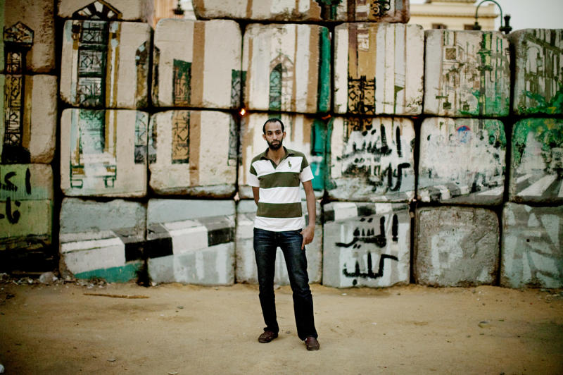 Karim, 29, no last name given, poses for a portrait in front of a security barrier near Tahrir Square, in Cairo, Egypt on Wednesday, May 23, 2012. Such barriers were decorated with graffiti art in recent months. On Wednesday morning, Egypt commenced two days of presidential voting after 16 months of interim rule by the Supreme Council of Armed Forces. This election is the first free and fair race since the ouster of former President Hosni Mubarak. (AP Photo/Pete Muller)