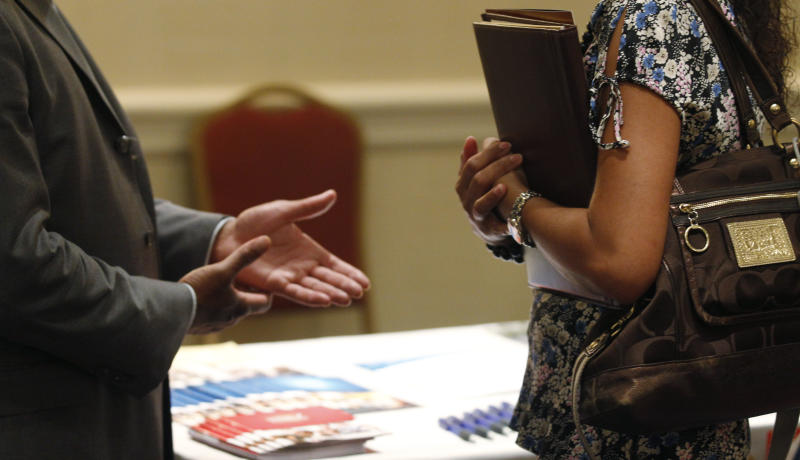 In this Monday, June 18, 2012, photo, a prospective employer, left, speaks with a prospective employee during a job fair, in Oak Brook, Ill.  A measure of future U.S. economic activity rose in May to the highest level in four years, a sign the economy will keep growing but at a modest pace. The Conference Board said Thursday, June 21, 2012, that its index of leading economic indicators rose 0.3 percent last month, after a 0.1 percent drop in April.  (AP Photo/M. Spencer Green)