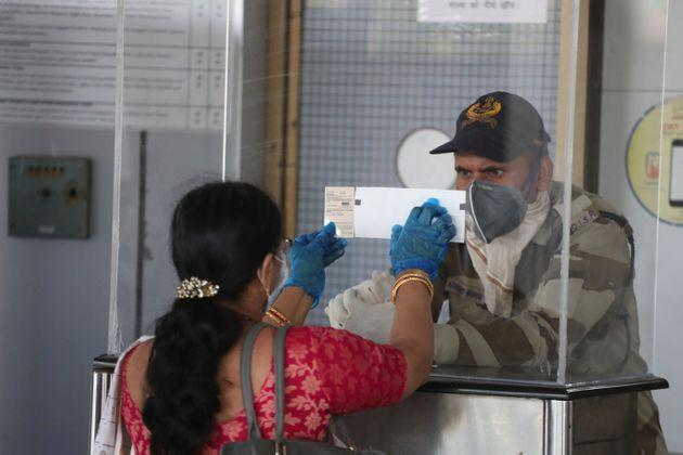 A passenger shows her ticket and identity card to a security personal at the airport in Ahmedabad on May 25, 2020.
