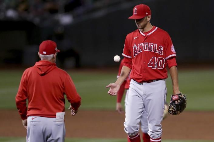 Los Angeles Angels pitcher Steve Cishek, right, is taken out of the game by manager Joe Maddon, left, during the sixth inning against the Oakland Athletics in a baseball game in Oakland, Calif., Tuesday, June 15, 2021. (AP Photo/Jed Jacobsohn)