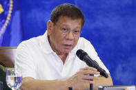 In this Monday, Feb. 15, 2021, photo provided by the Malacanang Presidential Photographers Division, Philippine President Rodrigo Duterte gestures as he meets members of the Inter-Agency Task Force on the Emerging Infectious Diseases in Davao city, southern Philippines. The Philippine president has approved an amnesty program for Muslim and communist rebels who would agree to surrender their weapons as they return to normal life in the latest such attempt to tame rural insurgencies that have raged for half a century. (Joey Dalumpines/Malacanang Presidential Photographers Division via AP)