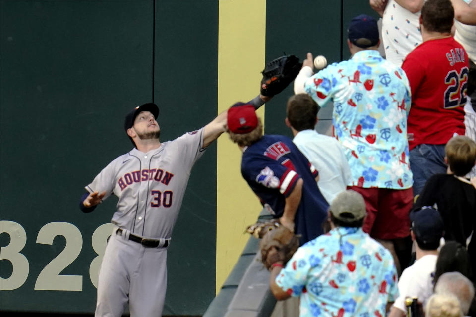 Houston Astros right fielder Kyle Tucker (30) reaches but cannot catch a foul ball off the bat of Minnesota Twins' Alex Kirilloff in the fourth inning of a baseball game, Saturday, June 12, 2021, in Minneapolis. (AP Photo/Jim Mone)