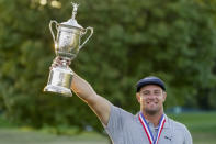 FILE - Bryson DeChambeau holds up the winner's trophy after winning the U.S. Open Golf Championship in Mamaroneck, N.Y., in this Sunday, Sept. 20, 2020, file photo. DeChambeau validated his move toward more distance when he was among the three major champions this year. (AP Photo/John Minchillo, File)
