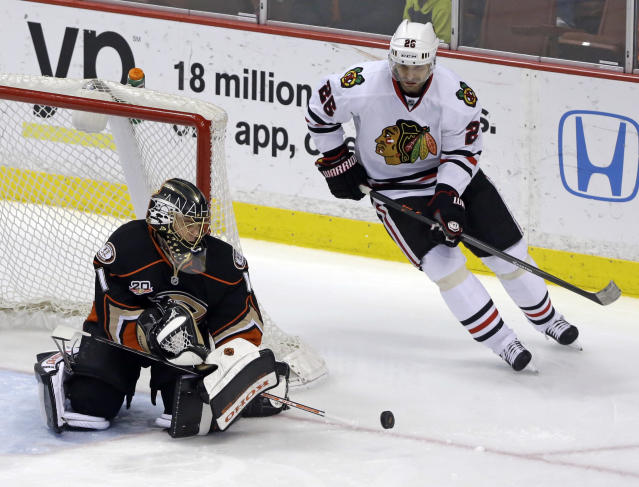 Anaheim Ducks goalie Jonas Hiller (1), of Switzerland, deflects the puck as Chicago Blackhawks center Michal Handzus (26), of the Czech Republic, skates past during the second period of an NHL hockey game in Anaheim, Calif., Wednesday, Feb. 5, 2014. (AP Photo/Reed Saxon)
