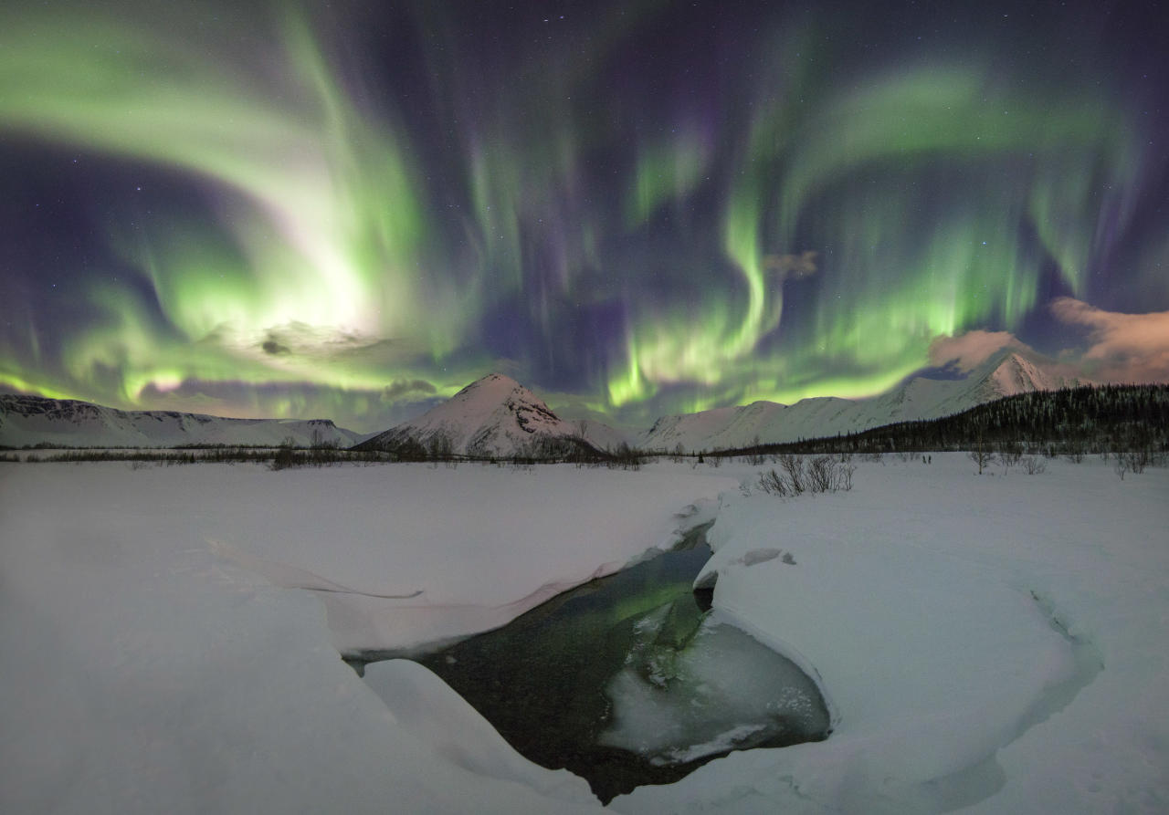 "<p>These Northern Lights ""rainbows"" have turned the sky greener than the Earth below. (Photo: Vitaly Istomin/Caters News) </p>"