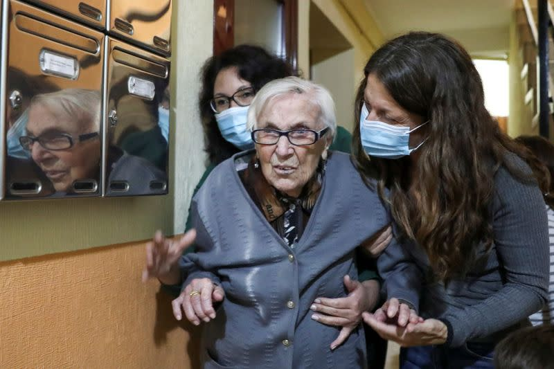 Florentina Martin, a 99 year-old woman who survived coronavirus disease (COVID-19), is helped by her caregiver Olga Arauz and her granddaughter Noelia Valle at the entrance of her home in Pinto