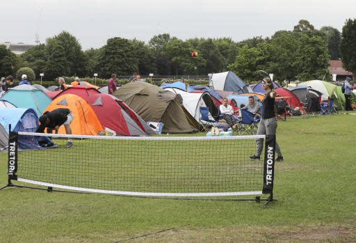 """In this Tuesday, July 9, 2019, some tennis fans play a game as they wait in line for tickets to enter the Wimbledon Tennis Championships in London. For many the Wimbledon experience starts in a tent as they gather in a small park across from the tournament grounds to camp out, some for days, in the hope of getting a ticket to Centre Court as they are released each day. """"The Queue"""" is a decades-old tradition that has grown to become its own phenomenon.(AP Photo/Natasha Livingstone)"""
