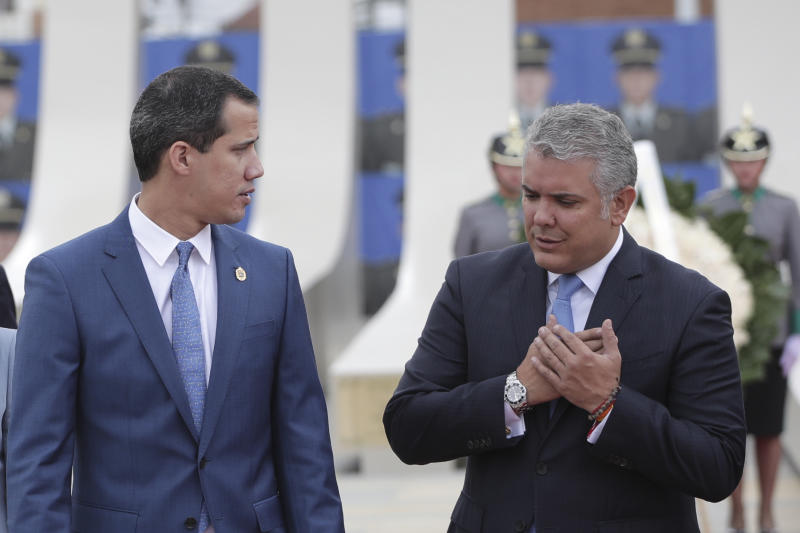 Colombian President Ivan Duque, right, talks to Venezuela's opposition leader Juan Guadio at a ceremony marking one year since a car bomb attack at the police academy, during the inauguration of a regional anti-terrorism summit in Bogota, Colombia, Friday, Jan. 20, 2020. Colombian government blames rebels of the National Liberation Army, ELN, for the bombing that killed at least 21 people on Jan. 17, 2019. (AP Photo/Ivan Valencia)