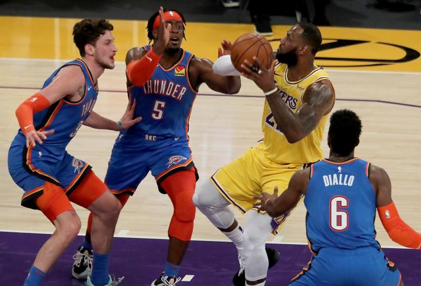 LOS ANGELES, CA. - FEB. 10, 2021. Lakers forward LeBron James goes to the basket against a trio of Thunder defenders in the first quarter of a game at Staples Center in Los Angeles on Wednesday night, Feb. 10, 2021. (Luis Sinco/Los Angeles Times)