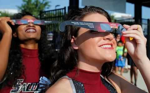 Cheerleaders use solar viewing glasses - Credit: Reuters