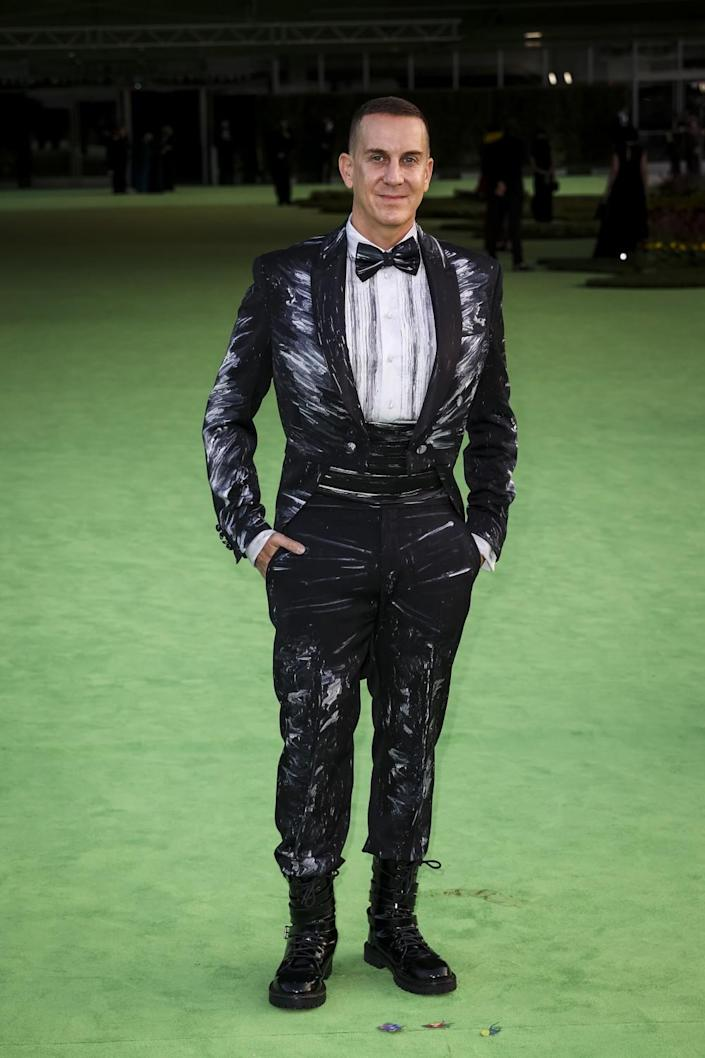 A man in a patterned black tuxedo and bow tie posing on a green carpet