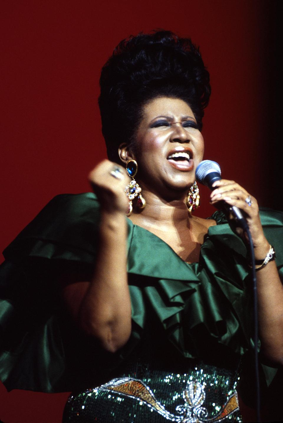 <p>Aretha Franklin performs onstage in 1986 wearing an extravagant green ruffle and metallic gown with chandalier jewel earrings and a larger-than-life pompadour. (Photo by Al Pereira/Michael Ochs Archives/Getty Images) </p>