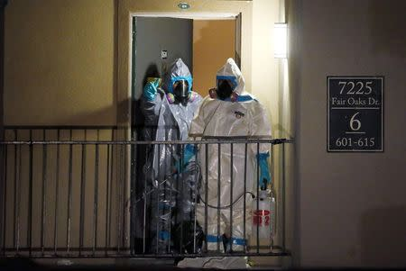 Workers in hazardous material suits step out of an apartment unit where a man diagnosed with the Ebola virus was staying in Dallas, Texas, October 5, 2014. REUTERS/Jim Young