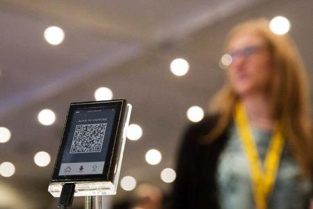A woman stands behind a digital Bitcoin wallet during the Inside Bitcoins: The Future of Virtual Currency Conference in New York