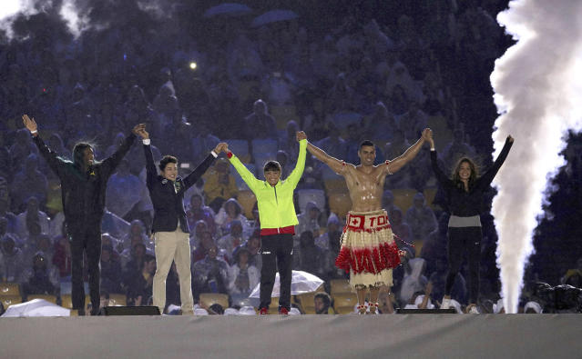 <p>Performers (including Tonga's flag bearer Pita Taufatofua) take part in the closing ceremony for the 2016 Rio Olympics. (REUTERS/Stoyan Nenov) </p>