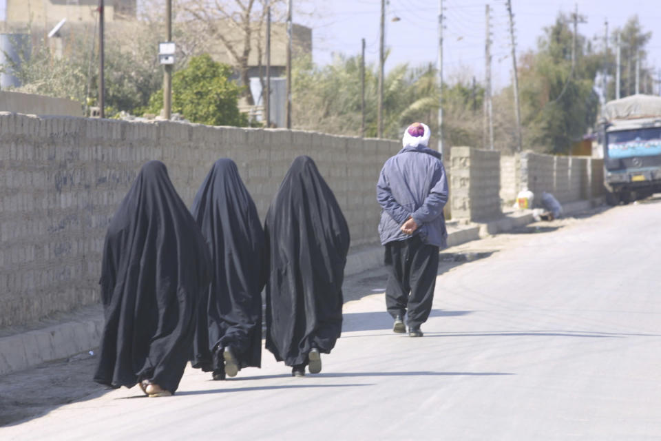 This February 2003 photo provided by photographer Murat Düzyol shows three women walking behind a man in Erbil, Iraq. A version of this original image was manipulated to digitally add chains on the women's ankles, with a caption erroneously claiming it was made in Afghanistan after the Taliban took control of the country in August 2021. (Murat Düzyol via AP)