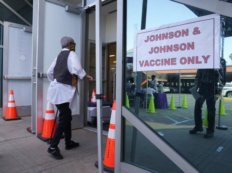 A person wearing a face mask walks into a vaccination site with a sign by the door reading