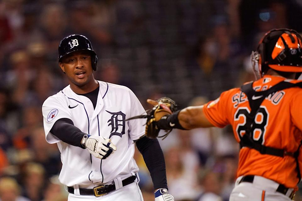 Detroit Tigers' Jonathan Schoop argues his strike call with umpire Ramon De Jesus as Baltimore Orioles catcher Pedro Severino walks off to celebrate the Orioles' 5-2 win after a baseball game, Saturday, July 31, 2021, in Detroit.