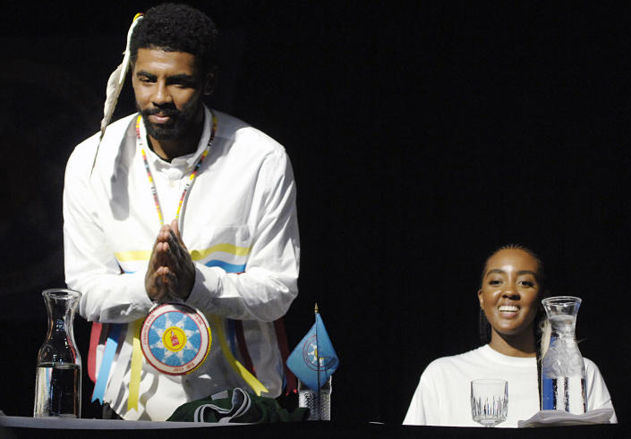 Boston Celtic point guard Kyrie Irving gestures his thanks to a group of students from Little Eagle, S.D. after they gave him a quilt during a naming ceremony in his honor, Thursday, Aug. 23, 2018 at the Prairie Knights Casino north of Fort Yates, N.D. on the Standing Rock Sioux Indian Reservation. Seated next to Irving is his older sister, Asia Irving. Irving's mother, Elizabeth Larson, was an enrolled member of the tribe before being adopted as a youngster. Irving was named Little Mountain by the tribe.(Mike McCleary/The Bismarck Tribune via AP)