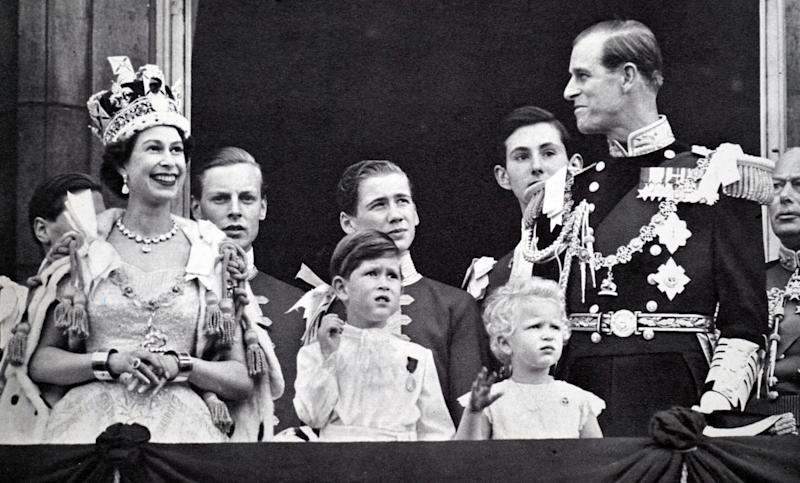 Buckingham Palace balcony. Coronation day 1953. The Queen and the Duke exchange smiles while Prince Charles and Princess Anne are absorbed with the planes roaring overhead. (Photo by: Universal History Archive/Universal Images Group via Getty Images)