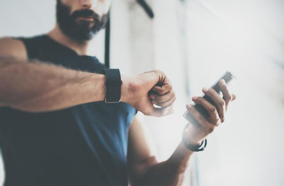 Close-up Shot Bearded Sportive Man After Workout Session Checks Fitness Results Smartphone.Adult Guy Wearing Sport Tracker Wristband Arm.Training hard inside gym.Horizontal bar background.Blurred - Image