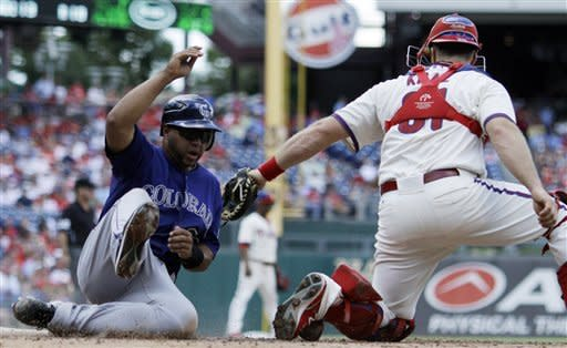 Colorado Rockies' Wilin Rosario, left, scores past Philadelphia Phillies catcher Erik Kratz on a single by DJ LeMahieu in the second inning of the first game of a baseball doubleheader on Sunday, Sept. 9, 2012, in Philadelphia. (AP Photo/Matt Slocum)