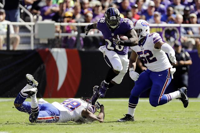 <p>Baltimore Ravens running back Terrance West (28) breaks a tackle by Buffalo Bills cornerback Ronald Darby (28) as he runs past Buffalo Bills middle linebacker Preston Brown (52) during the first half of an NFL football game in Baltimore, Sunday, Sept. 11, 2016. (AP Photo/Patrick Semansky) </p>