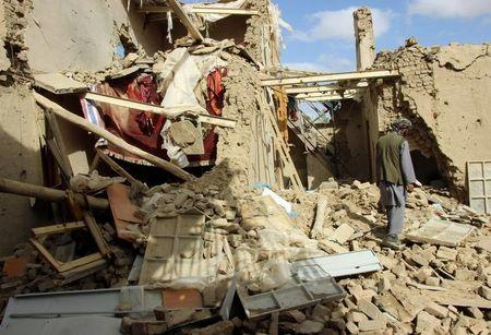 An Afghan man inspects a house destroyed during an air strike called in to protect Afghan and U.S. forces during a raid on suspected Taliban militants, in Kunduz