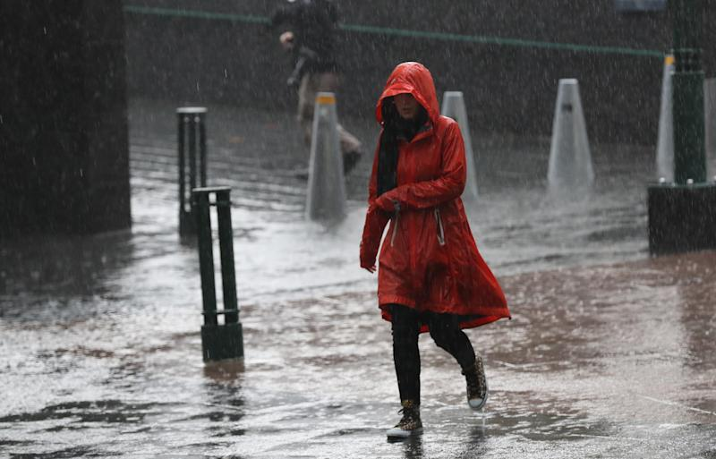 Pedestrians are seen in the rain on Southbank in Melbourne, Friday, May 10, 2019. The forecast rainfall is part of a vigorous cold front that will deliver rain to much of Victoria. (AAP Image/David Crosling) NO ARCHIVING
