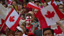 An England supporter (C) is surrounded by Canadian flags during the match between England and Canada at the 2015 FIFA Women's World Cup at BC Place Stadium in Vancouver on June 27, 2015 (AFP Photo/Andy Clark)