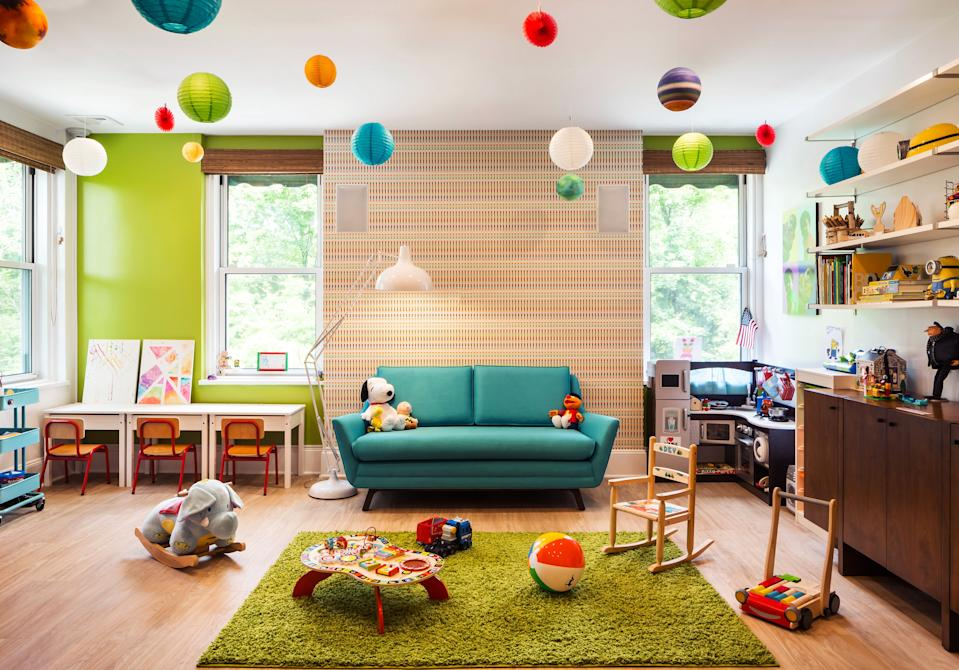 """<div class=""""caption""""> The playroom is a riot of color. """"I try to sneak some wallpaper into every project, if I can,"""" says McLeod. Here, she chose a multicolored print from <a href=""""https://www.stylelibrary.com/"""" rel=""""nofollow noopener"""" target=""""_blank"""" data-ylk=""""slk:Style Library"""" class=""""link rapid-noclick-resp"""">Style Library</a> and paired it with an accent wall painted <a href=""""https://www.benjaminmoore.com/en-us"""" rel=""""nofollow noopener"""" target=""""_blank"""" data-ylk=""""slk:Benjamin Moore"""" class=""""link rapid-noclick-resp"""">Benjamin Moore</a>'s Tequila Lime. The loveseat is from <a href=""""https://joybird.com/"""" rel=""""nofollow noopener"""" target=""""_blank"""" data-ylk=""""slk:Joybird"""" class=""""link rapid-noclick-resp"""">Joybird</a>, the rug from <a href=""""https://www.wayfair.com/"""" rel=""""nofollow noopener"""" target=""""_blank"""" data-ylk=""""slk:Wayfair"""" class=""""link rapid-noclick-resp"""">Wayfair</a>, and the children's desks and shelves are from <a href=""""https://www.ikea.com/us/en/"""" rel=""""nofollow noopener"""" target=""""_blank"""" data-ylk=""""slk:IKEA"""" class=""""link rapid-noclick-resp"""">IKEA</a>. The sideboard was repurposed from the client's previous home. </div>"""