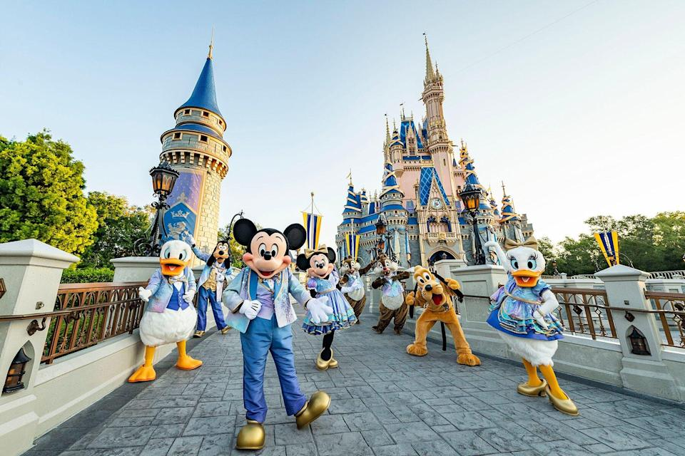 The characters celebrating Walt Disney World Resort's 50th anniversary in front of Cinderellas Castle