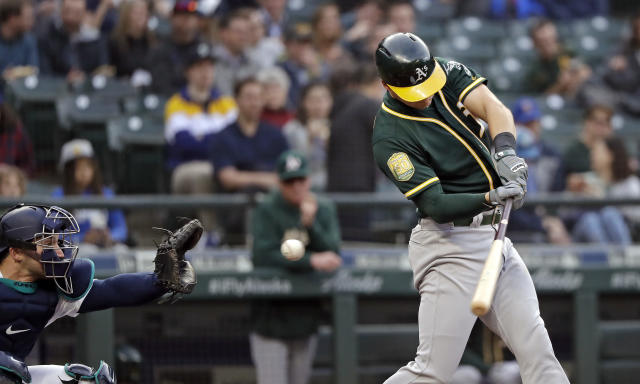 Oakland Athletics' Chad Pinder swings and misses to strike out as Seattle Mariners catcher Mike Zunino waits to catch the pitch during the first inning of a baseball game Wednesday, May 2, 2018, in Seattle. (AP Photo/Elaine Thompson)