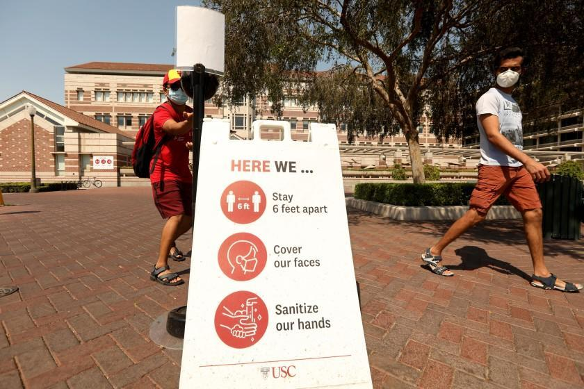 LOS ANGELES, CA - AUGUST 17, 2020 - - USC student Ashish Kulkarni, 24, takes a handful of antibacterial gel, as student Vijay Ugru, 25, looks over three steps to keep the coronavirus at bay on the first day of academic instruction for the Fall 2020 semester on the USC campus in Los Angeles on August 17, 2020. Students were taking online courses off campus due to the coronavirus pandemic and the university was nearly empty. (Genaro Molina / Los Angeles Times)