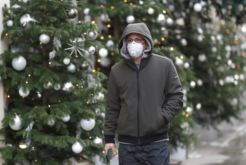 FILE PHOTO: A man walks past Christmas decorations outside a store amid the coronavirus disease (COVID-19) outbreak in London