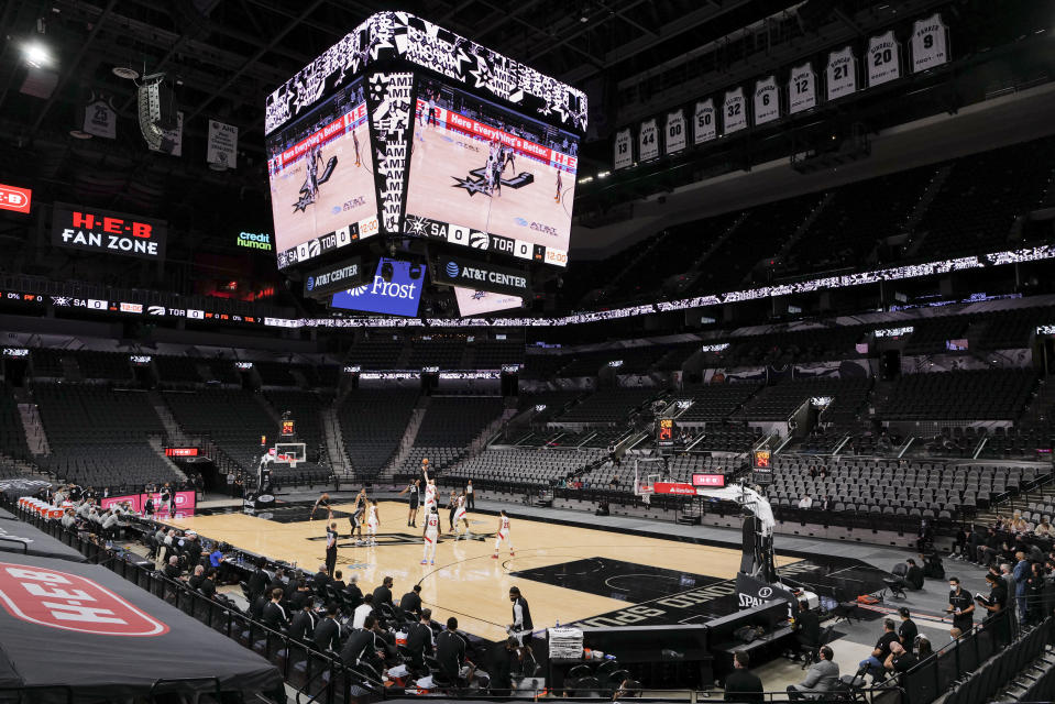 The Toronto Raptors and San Antonio Spurs tip off at the start of an NBA basketball game, Saturday, Dec. 26, 2020, in San Antonio. As a precaution intended to prevent the spread of COVID-19, there were no spectators allowed. San Antonio won 119-114. (AP Photo/Darren Abate)