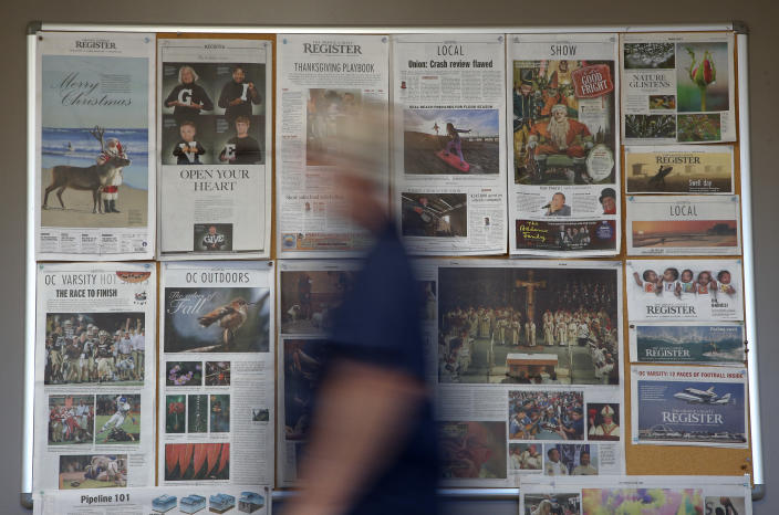 Some front pages and section fronts of the Orange County Register are seen in the newsroom in Santa Ana, Calif., Thursday, Dec. 27, 2012. After years of demoralizing layoffs, one newspaper is trying something novel: hiring more reporters. The Orange County Register's new owner thinks the way to turn the paper around is through better reporting to lure new and former readers to a revived product. (AP Photo/Jae C. Hong)